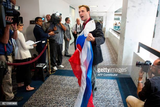 Ryan Clayton of Americans Take Action speaks to reporters after attempting to push a Russian flag into the face of Jared Kushner US President Donald...