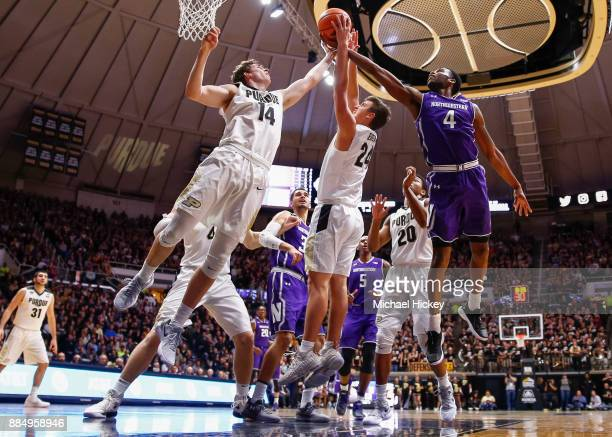Ryan Cline and Grady Eifert of the Purdue Boilermakers battle for the rebound with Vic Law of the Northwestern Wildcats at Mackey Arena on December 3...