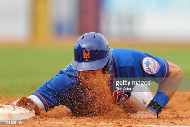 Ryan Cordell of the New York Mets dives safely back into first base on a pick off attempt the Houston Astros during the fifth inning of a spring...