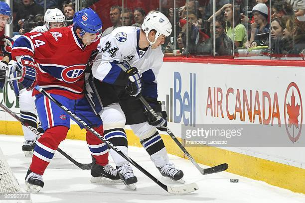 Ryan Craig of Tampa Bay Lightning battles for the puck possession with Tomas Plekanec of the Montreal Canadiens during the NHL game on November 07...