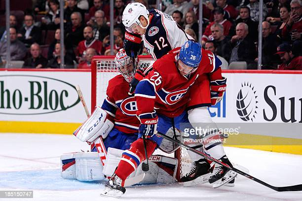 Ryan Craig of the Columbus Blue Jackets attempts to deflect the puck in front of Josh Gorges and Carey Price of the Montreal Canadiens during the NHL...