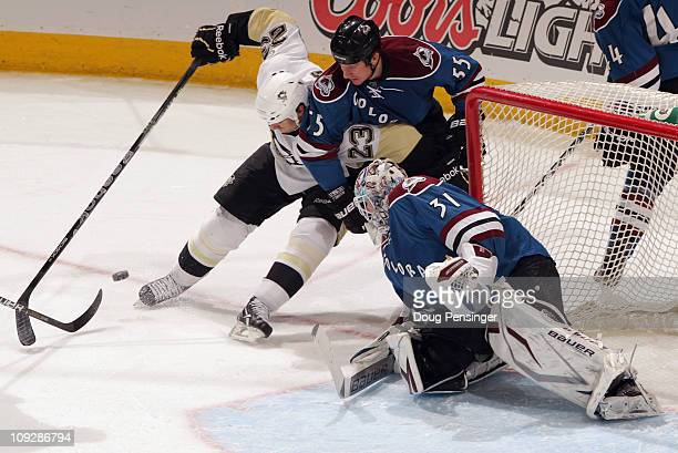 Ryan Craig of the Pittsburgh Penguins controls the puck against Cody McLeod of the Colorado Avalanche as goalie Peter Budaj of the Avalanche defends...