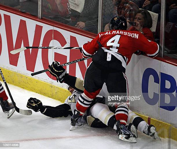 Ryan Craig of the Pittsburgh Penguins is knocked to the ice by Niklas Hjalmarsson of the Chicago Blackhawks at the United Center on February 20 2011...
