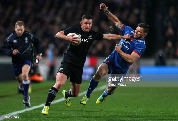 Ryan Crotty of New Zealand fends the tackle of Remy Grasso of France during the International Test match between the New Zealand All Blacks and...