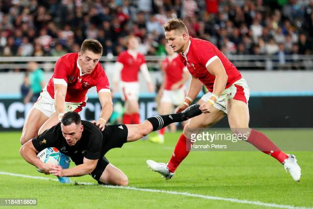 Ryan Crotty of New Zealand touches down to score his team's fifth try under pressure from Josh Adams and Hallam Amos of Wales during the Rugby World...