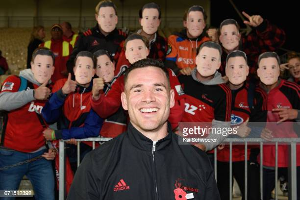 Ryan Crotty of the Crusaders poses in front of Crusaders fans wearing Ryan Crotty masks following the round nine Super Rugby match between the...