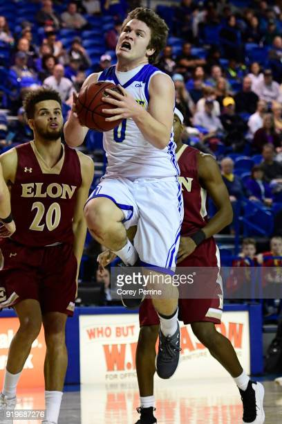 Ryan Daly of the Delaware Fightin Blue Hens drives to the basket as Sheldon Eberhardt of the Elon Phoenix looks on during the first half at the Bob...