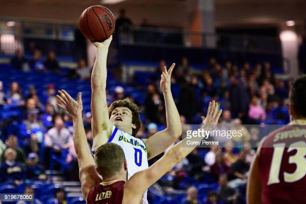 Ryan Daly of the Delaware Fightin Blue Hens shoots over Collin Luther of the Elon Phoenix during the first half at the Bob Carpenter Center on...