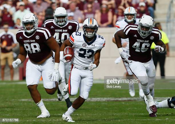 Ryan Davis of the Auburn Tigers rushes away from Kingsley Keke of the Texas AM Aggies and Landis Durham at Kyle Field on November 4 2017 in College...