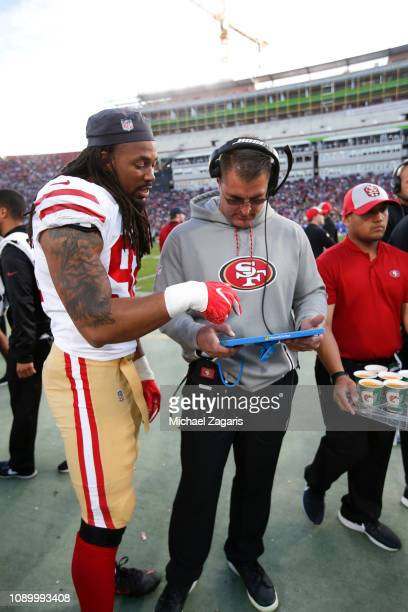 Ryan Delaire and Defensive Line Coach Jeff Zgonina of the San Francisco 49ers talk on the sideline during the game against the Los Angeles Rams at...
