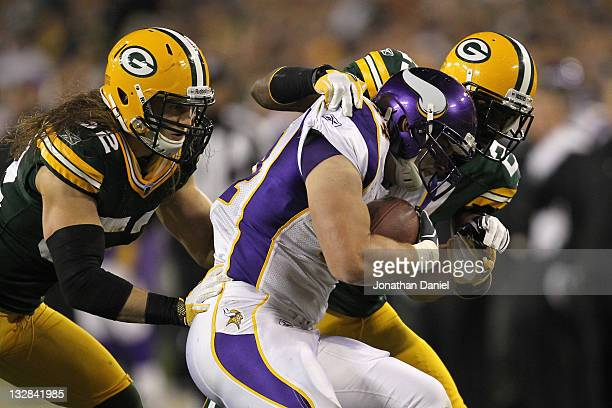 Ryan D'Imperio of the Minnesota Vikings is bought down by Charles Woodson and Clay Matthews of the Green Bay Packers at Lambeau Field on November 14...