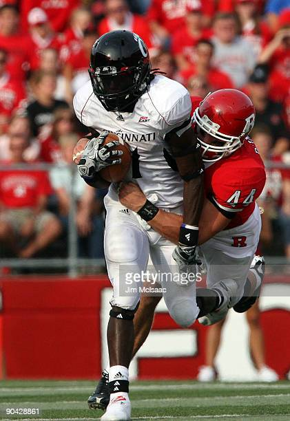 Ryan D'Imperio of the Rutgers Scarlet Knights tackles Mardy Gilyard of the Cincinnati Bearcats at Rutgers Stadium on September 7 2009 in Piscataway...
