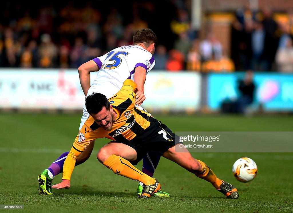 Ryan Donaldson of Cambridge is pushed off the ball by Oxford's Joe Riley during the Sky Bet League Two match between Cambridge United and Oxford United at The Abbey Stadium on October 11, 2014 in Cambridge, England.