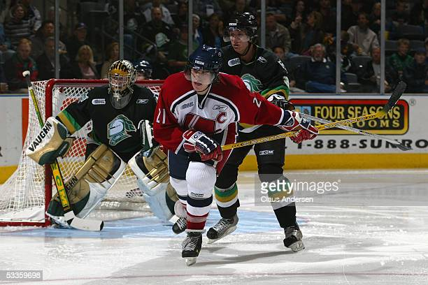 Ryan Donally of the Windsor Spitfires skates past goalie Ryan MacDonald and Marc Methot of the London Knights during a Ontario Hockey League game at...