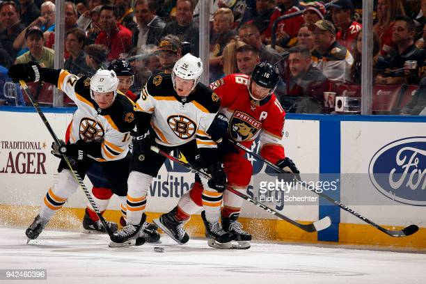 Ryan Donato of the Boston Bruins and teammate Colby Cave skate for possession against Aleksander Barkov of the Florida Panthers at the BBT Center on...