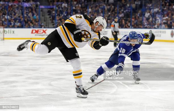 Ryan Donato of the Boston Bruins shoots past the defense of Ondrej Palat of the Tampa Bay Lightning during the first period of the game at the Amalie...