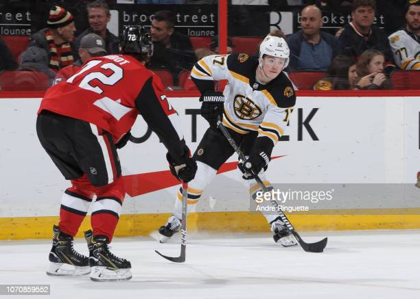 Ryan Donato of the Boston Bruins stickhandles the puck against Thomas Chabot of the Ottawa Senators at Canadian Tire Centre on December 9 2018 in...