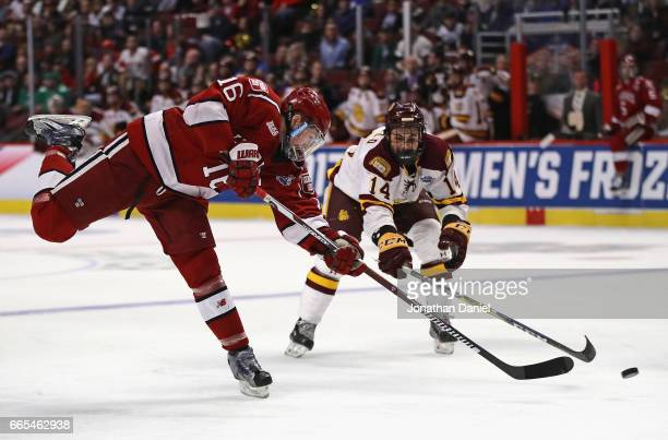 Ryan Donato of the Harvard Crimson gets off a shot past Alex Iafallo of the MinnesotaDuluth Bulldogs during game one of the 2017 NCAA Division I...