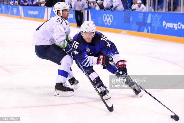 Ryan Donato of the United States controls the puck against Mitja Robar of Slovenia during the Men's Ice Hockey Preliminary Round Group B game on day...