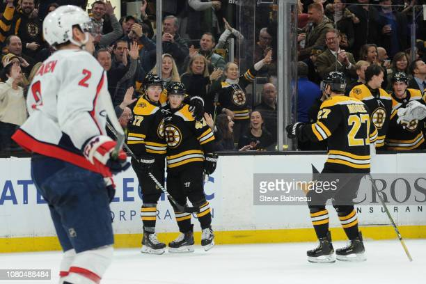Ryan Donato Torey Krug and John Moore of the Boston Bruins celebrate a goal against the Washington Capitals at the TD Garden on January 10 2019 in...