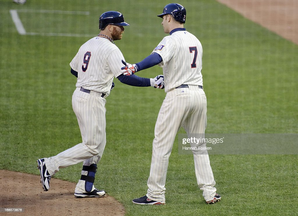 Ryan Doumit #9 and Joe Mauer #7 of the Minnesota Twins celebrate scoring on a two run home run against the Baltimore Orioles by Doumit during the sixth inning of the game on May 11, 2013 at Target Field in Minneapolis, Minnesota.