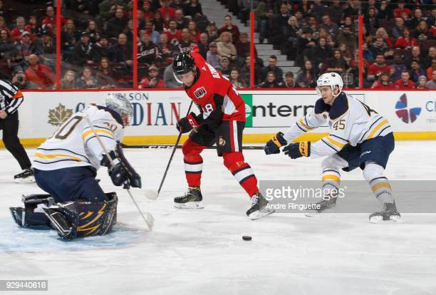 Ryan Dzingel of the Ottawa Senators is stopped on a scoring chance by Robin Lehner and Brendan Guhle of the Buffalo Sabres at Canadian Tire Centre on...