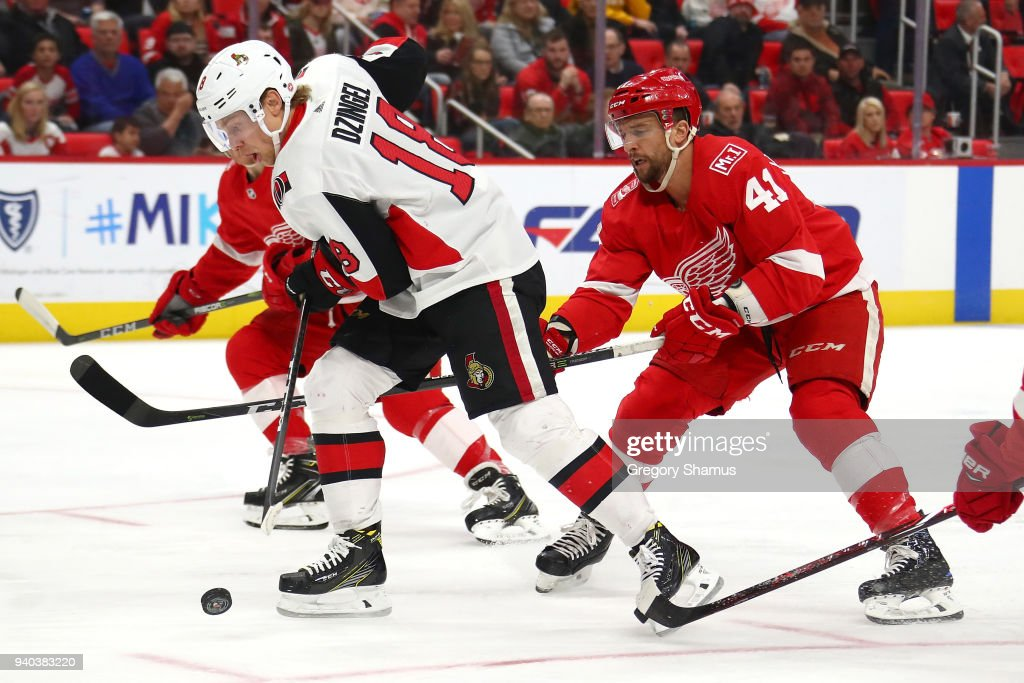 Ryan Dzingel #18 of the Ottawa Senators tries to control the puck in front of Luke Glendening #41 of the Detroit Red Wings during the first period at Little Caesars Arena on March 31, 2018 in Detroit, Michigan.