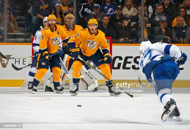 Ryan Ellis and Nick Bonino of the Nashville Predators stand in front of goalie Pekka Rinne to block a shot by Ryan McDonagh of the Tampa Bay...