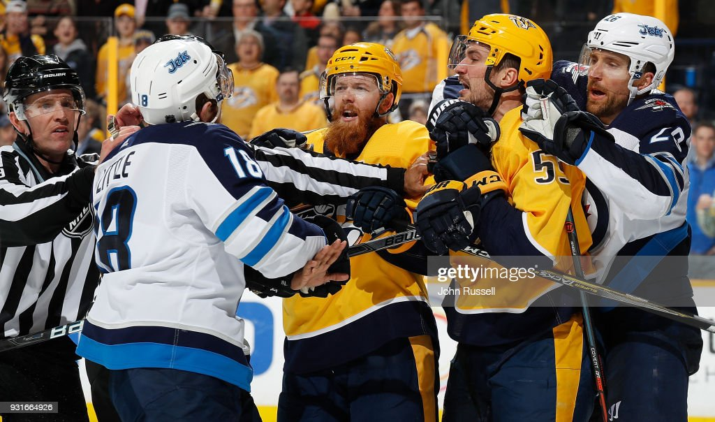 Ryan Ellis #4 and Roman Josi #59 of the Nashville Predators argue with Bryan Little #18 and Blake Wheeler #26 of the Winnipeg Jets during an NHL game at Bridgestone Arena on March 13, 2018 in Nashville, Tennessee.