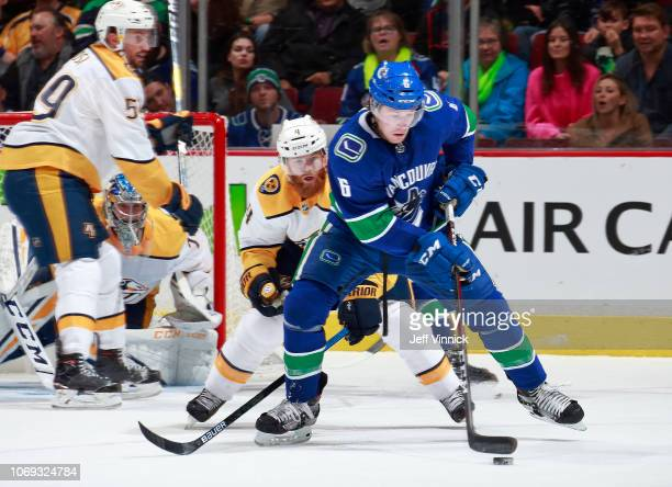 Ryan Ellis of the Nashville Predators checks Brock Boeser of the Vancouver Canucks during their NHL game at Rogers Arena December 6, 2018 in...