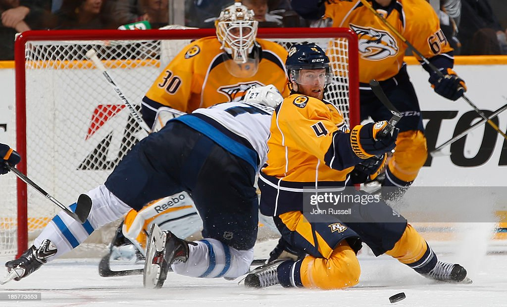 Ryan Ellis #4 of the Nashville Predators clears the puck against Eric Tangradi #27 of the Winnipeg Jets at Bridgestone Arena on October 24, 2013 in Nashville, Tennessee.