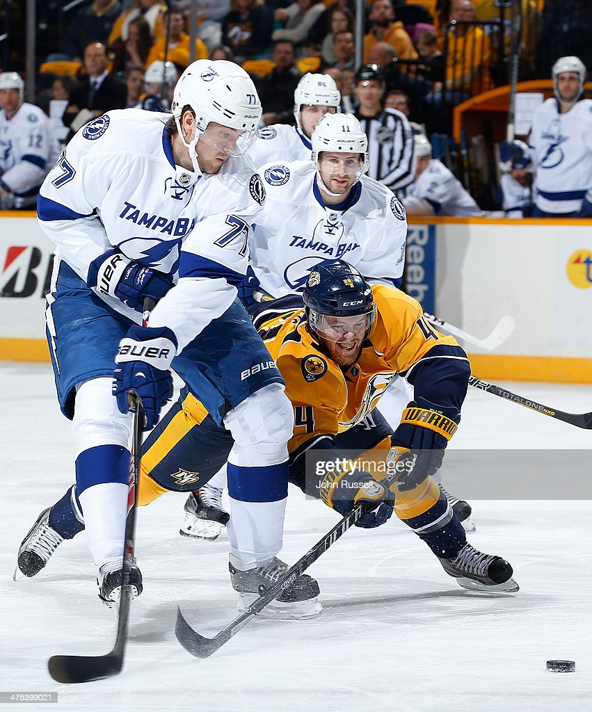 Ryan Ellis #4 of the Nashville Predators dives for the puck against Victor Hedman #77 of the Tampa Bay Lightning at Bridgestone Arena on February 27, 2014 in Nashville, Tennessee.