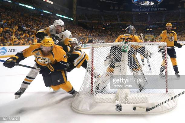 Ryan Ellis of the Nashville Predators falls to the ice against Evgeni Malkin and Patric Hornqvist of the Pittsburgh Penguins during the first period...