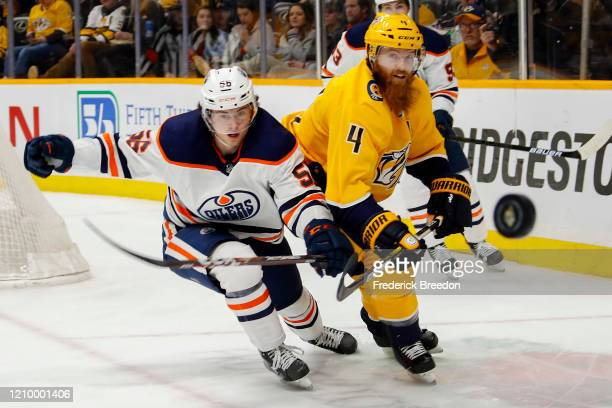 Ryan Ellis of the Nashville Predators flips a puck past Kailer Yamamoto of the Edmonton Oilers during the second period at Bridgestone Arena on March...