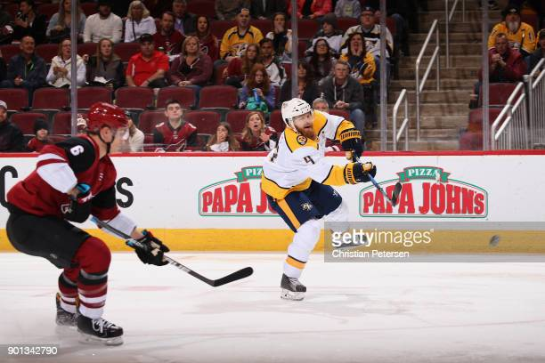 Ryan Ellis of the Nashville Predators shoots the puck ahead of Jakob Chychrun of the Arizona Coyotes during the first period of the NHL game at Gila...