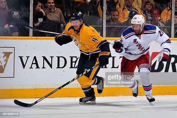 Ryan Ellis of the Nashville Predators ties up the stick of Dominic Moore of the New York Rangers at Bridgestone Arena on November 23 2013 in...
