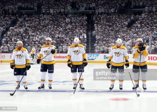 Ryan Ellis Roman Josi Austin Watson Colton Sissons and Nick Bonino of the Nashville Predators stand on the ice prior to puck drop against the...