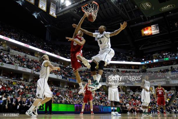 Ryan Evans of the Wisconsin Badgers dunks against Adreian Payne of the Michigan State Spartans during their Semifinal game of the 2012 Big Ten Men's...