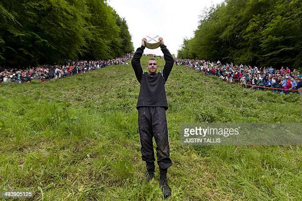 Ryan Fairley from England celebrates after winning a race down Coopers Hill in pursuit of a Double Gloucester cheese during the annual cheese rolling...
