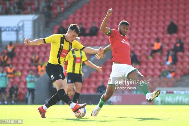 Ryan Fallowfield of Harrogate Town crosses the ball whilst under pressure from Zak Jules of Walsall during the Sky Bet League Two match between...