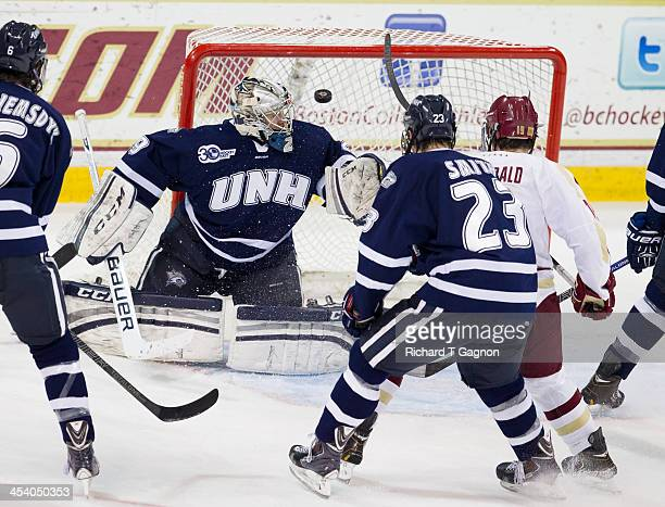 Ryan Fitzgerald of the Boston College Eagles, Kyle Smith and Casey DeSmith of the New Hampshire Wildcats watch the puck enter the net on a shot by...
