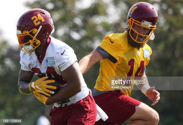 Ryan Fitzpatrick hands off to Antonio Gibson of the Washington Football Team during the Washington Football Team training camp on July 28, 2021 in...