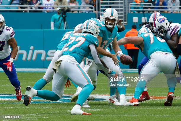 Ryan Fitzpatrick hands the ball off to Kalen Ballage of the Miami Dolphins against the Buffalo Bills during an NFL game on November 17, 2019 at Hard...