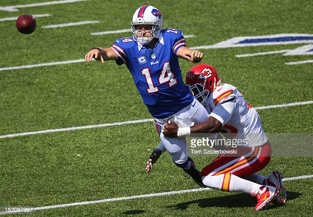 Ryan Fitzpatrick of the Buffalo Bills throws during an NFL game as he is tackled by Justin Houston of the Kansas City Chiefs at Ralph Wilson Stadium...