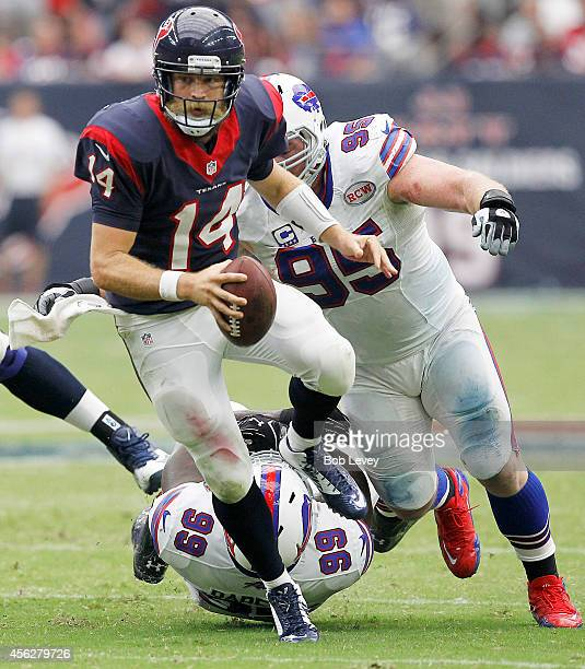 Ryan Fitzpatrick of the Houston Texans breaks the tackle of Marcell Dareus of the Buffalo Bills in the fourth quarter in a NFL game on September 28...