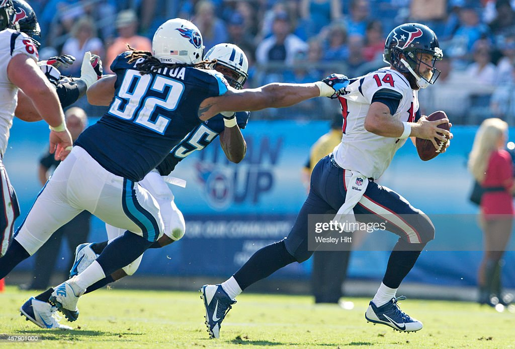 Ryan Fitzpatrick #14 of the Houston Texans is grabbed by the back of his jersey by Ropait Pitoitua #92 of the Tennessee Titans at LP Field on October 26, 2014 in Nashville, Tennessee. The Texans defeated the Titans 30-16.