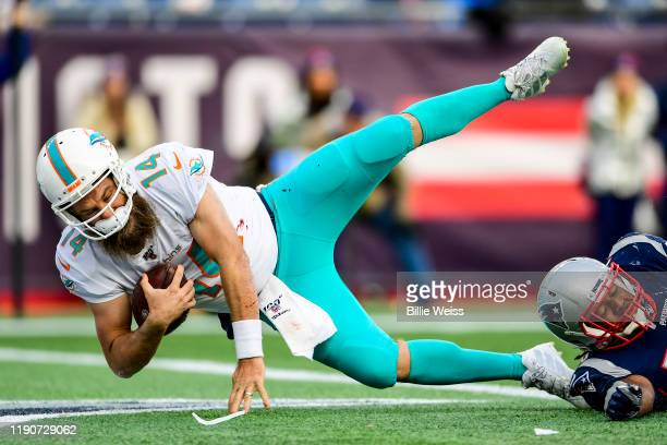 Ryan Fitzpatrick of the Miami Dolphins carries the ball for a touchdown during the third quarter of a game against the New England Patriots at...