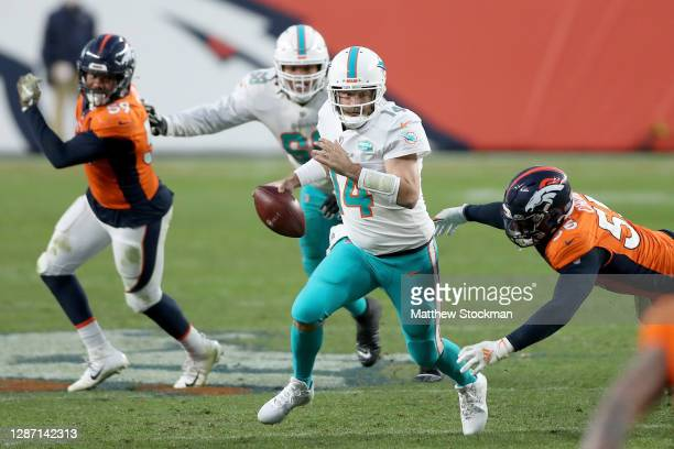 Ryan Fitzpatrick of the Miami Dolphins falls as he is tackled by Bradley Chubb of the Denver Broncos during the fourth quarter at Empower Field At...