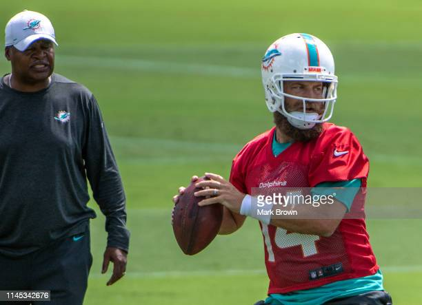 Ryan Fitzpatrick of the Miami Dolphins performing drills as Assistant Head Coach Jim Caldwell looks on during the second week of OTAs at Baptist...