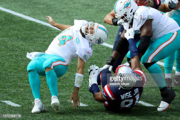 Ryan Fitzpatrick of the Miami Dolphins reacts after being hit by Deatrich Wise Jr. #91 of the New England Patriots during the first half at Gillette...